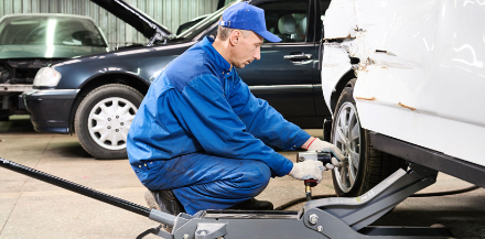 Mechanic changing tire for NYS inspection